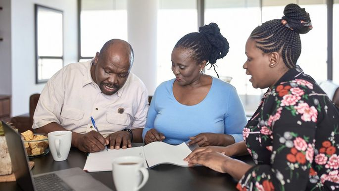 African mature Couple signing a retirement contract with financial advisor at home