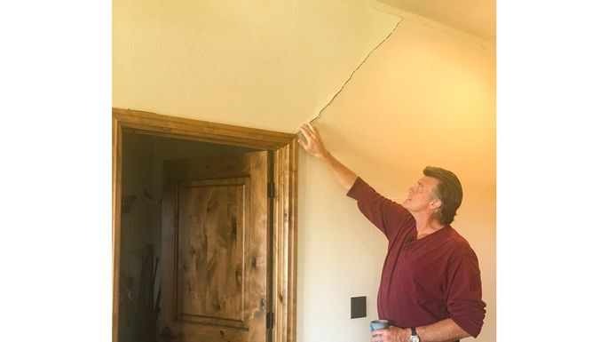 Mike Hazlip pointing out damage in his house.