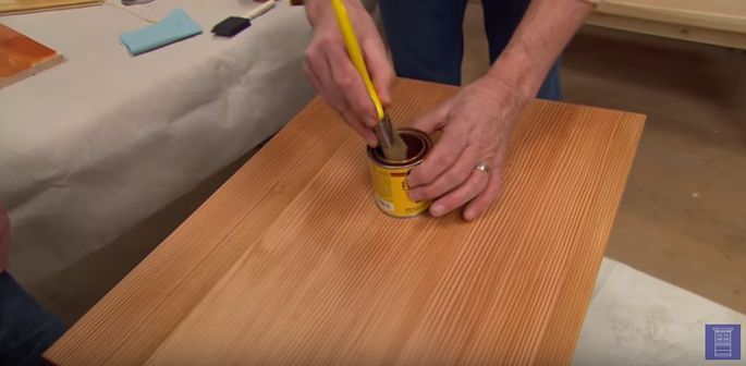 Stir the stain to incorporate any sediment stuck to the bottom of the can.