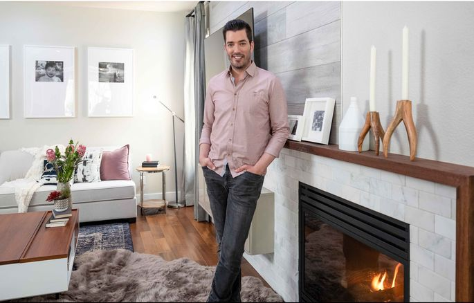 Jonathan is proud of the freshly oiled mantel, and the accent wall lined with high-end, wood-look vinyl flooring.