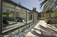This Glass Showcase Garage Keeps Dust Out, Lets Desert Views In