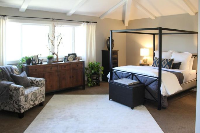 A new modern bed frame, gray walls, and white ceiling completely transform this master bedroom.
