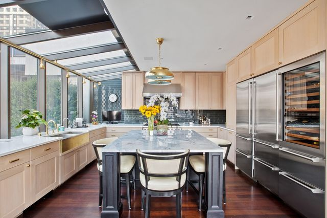 The apartment is listed with Howard Margolis, Jeff Adler and Marie Espinal of the Margolis Team at Douglas Elliman. DOUGLAS ELLIMAN REAL ESTATE Al Kahn, the licensing executive who introduced Pokémon and other animated series imports, is selling his four-story penthouse in Midtown Manhattan for $18.95 million. DOUGLAS ELLIMAN REAL ESTATE Mr. Kahn bought the property for about $5.4 million in 2012. He and his wife, actress and writer Jillian Crane, spent about $4 million to undergo a 2½-year renovation on the property. DOUGLAS ELLIMAN REAL ESTATE The couple, who were still engaged when they closed on the apartment, learned they both have a love of Art Deco-style furnishings, which they used throughout the space. A Julian Schnabel painting is displayed. DOUGLAS ELLIMAN REAL ESTATE Every lighting fixture in the apartment is an antique find from Italy or France, Mr. Kahn says. Much of the furniture is inspired by the French Art Deco movement of the 1930s and beyond. Furnishings are not included, but may be negotiable. DOUGLAS ELLIMAN REAL ESTATE An Art Deco-inspired glass and mahogany bar in the living area DOUGLAS ELLIMAN REAL ESTATE The living, dining and kitchen areas are spread across a single floor in the four-story apartment. DOUGLAS ELLIMAN REAL ESTATE A dining area overlooking the city skyline. DOUGLAS ELLIMAN REAL ESTATE The kitchen. The couple used cherry wood floors throughout the space.