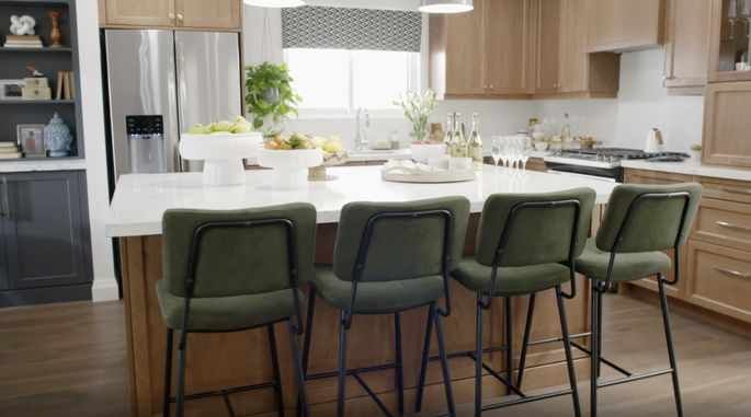 The brothers used wood tones and green chairs around the island for a colorful look.