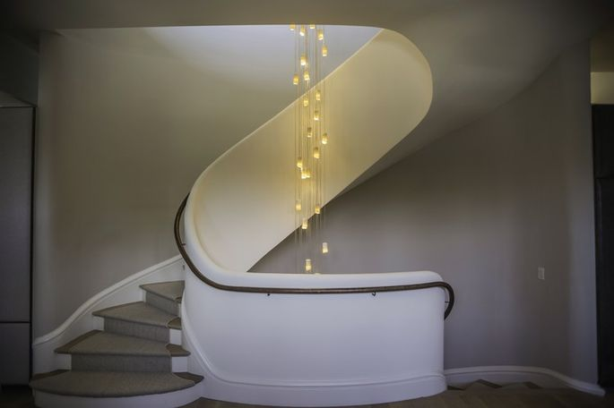 The curving, sculptural stairway is made from white plaster, a look inspired by New York's Guggenheim Museum. A sculptural light fixture extends 30 feet from the second-floor ceiling down a stairwell to the basement.