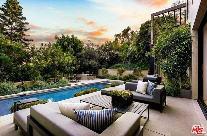 Lush trees offer privacy around the couple's outdoor seating and pool.