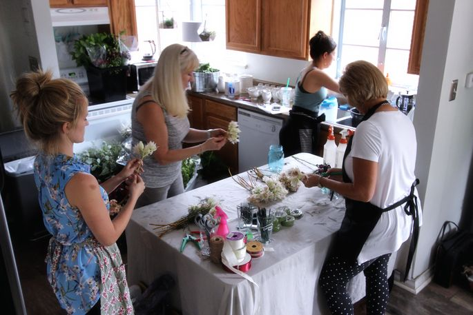 With her bridesmaid and some family members, Amy Wickberg, left, works on flower arrangementsin herkitchen.