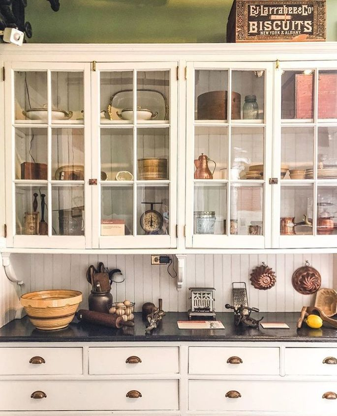 An antique scale and copper coffee pot add interest to this kitchen cabinet.
