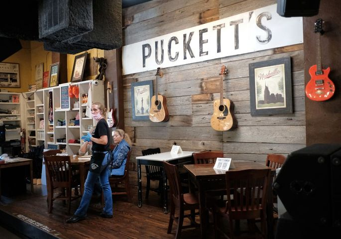 Tennessee is allowing restaurants to open at 50% capacity. Here, a waitress wears rubber gloves and a mask at Puckett's Grocery & Restaurant in Franklin, just outside Nashville.