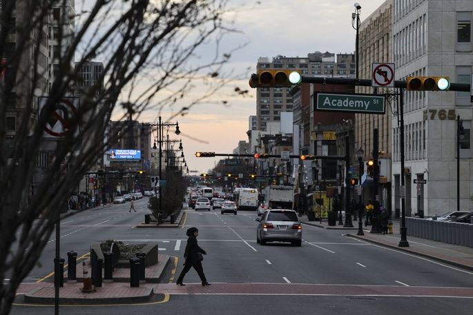 A pedestrian crosses a street in downtown Newark, New Jersey, U.S., on Wednesday, Nov. 25, 2020. Newark, New Jerseys largest city, issued a stay-at-home advisory from November 25 to December 4, shutting down all non essential businesses to curb the rising Covid-19 cases. Photographer: Angus Mordant/Bloomberg via Getty Images