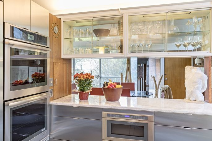 The Bentels' remodel preserved the layout of the circa-1957 kitchen, and some of its original features, like the suspended metal and glass cabinet.