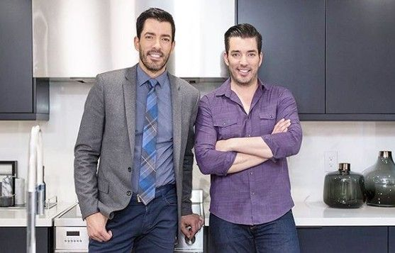 Drew and Jonathan Scott are happy with a remodeled black-and-white kitchen in which the red fire extinguisher has been discreetly tucked away.