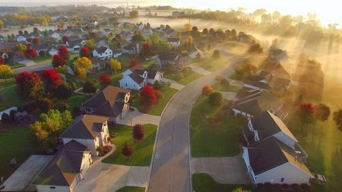 Idyllic Autumn neighborhood shrouded in fog at dawn.