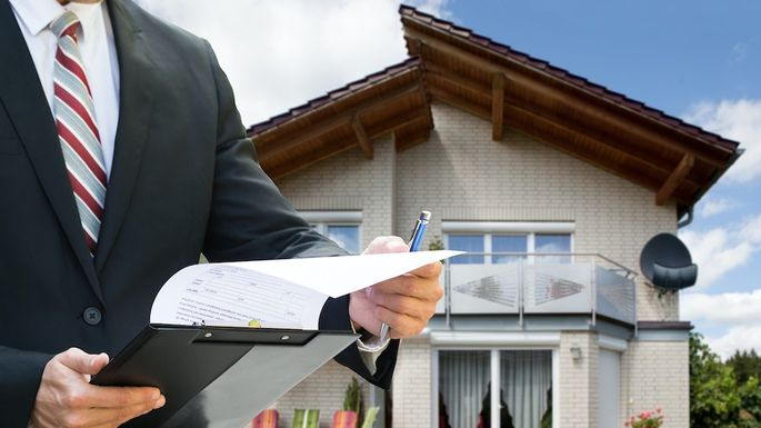 Man Checking Documents Standing Near House