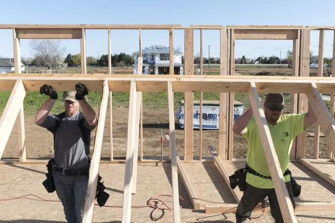 Workers install part of the frame of a new building in the Hammett Homes subdivision in Meridian, Idaho.