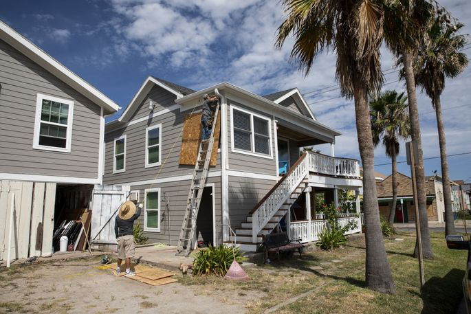 Workers place plywood over the windows of a home ahead of Hurricane Laura's arrival in Galveston, TX.