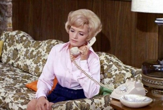 The avocado and cream brocade sofa that Carol Brady is sitting on is in high demand.
