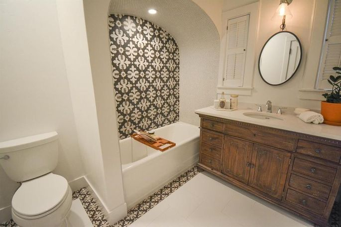 Mosaic tiles and a wooden vanity give this space life.