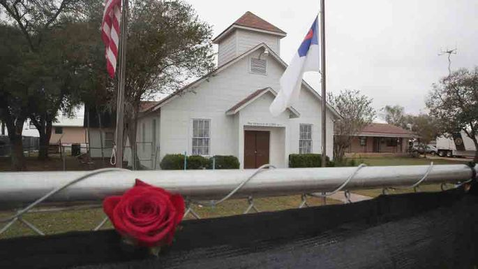 A rose is left in the fence surrounding the First Baptist Church of Sutherland Springs