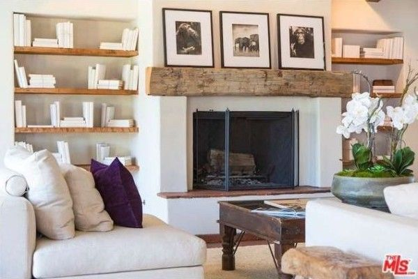 The fireplace with chunky wood mantel is the focus of the living room.