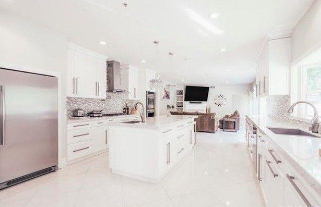 La cuisine comprend des comptoirs en marbre et des appareils en acier inoxydable.