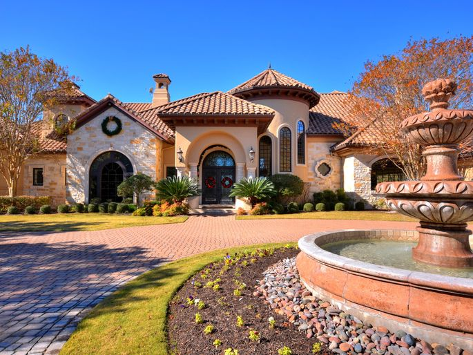Front exterior, circular driveway, and fountain