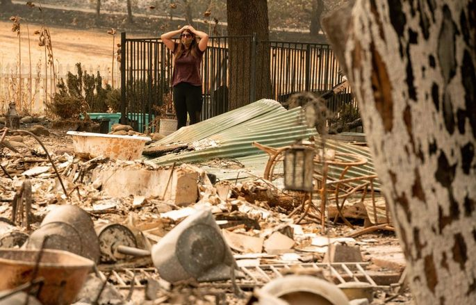 Alyssa Medina looks over the charred remains of her family home during the LNU Lightning Complex fire in Vacaville, CA.