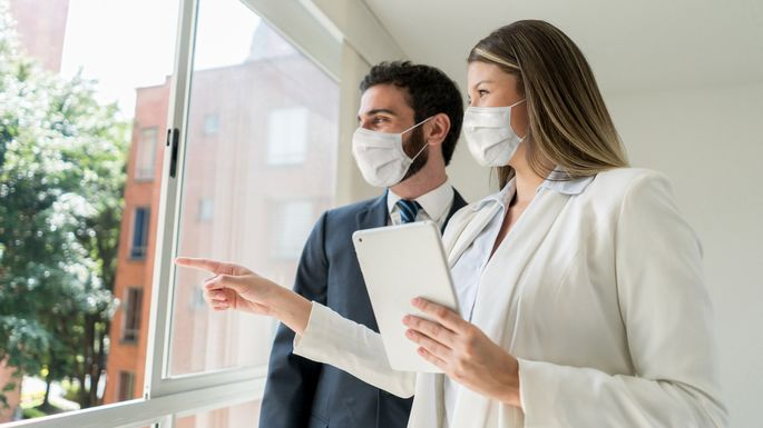 Beautiful real estate agent pointing at the view to customer both looking very cheerful but wearing protective face masks