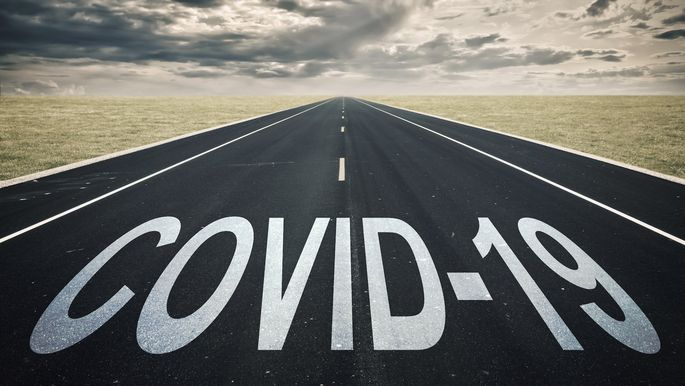 Covid-19 written on a road, dark clouds, coronavirus epidemic crisis concept