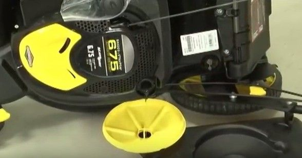 Empty the old oil from the lawn mower by turning it on its side.