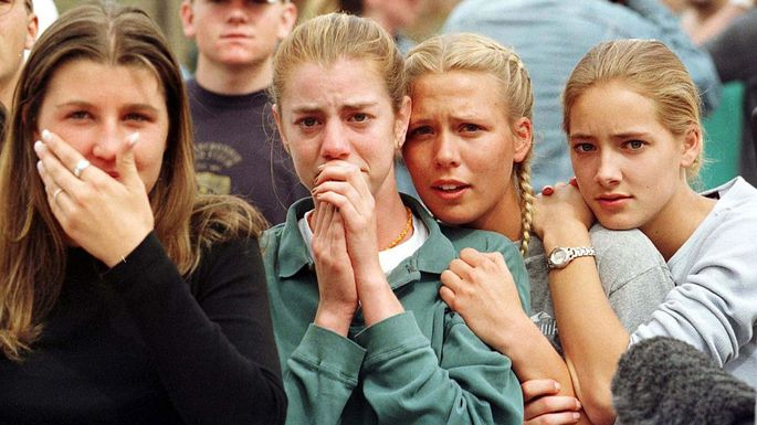 Students from Columbine High School watch as the last of their fellow students are evacuated from the school building in April 1999