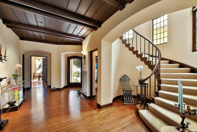 Vintage details include the curved stairs, sconces, and wood paneling.