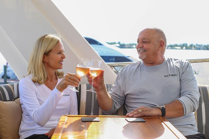The Hubbards enjoy a glass of rosé on the deck of their yacht.