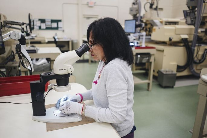Daisy Rivera, a quality inspector, checks for defects in electronic connectors at Plastikos.