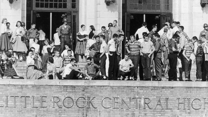 National Guardsmen and a group of white students standing outside Little Rock Central High School to prevent African-American students from entering