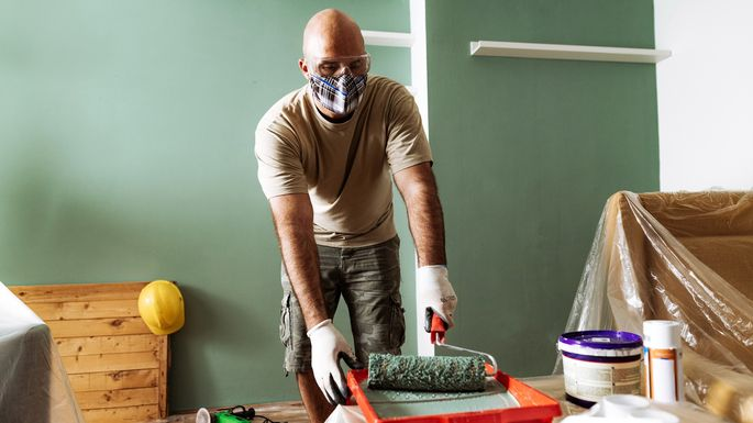 Renovation at home - man preparing the paint for second coat