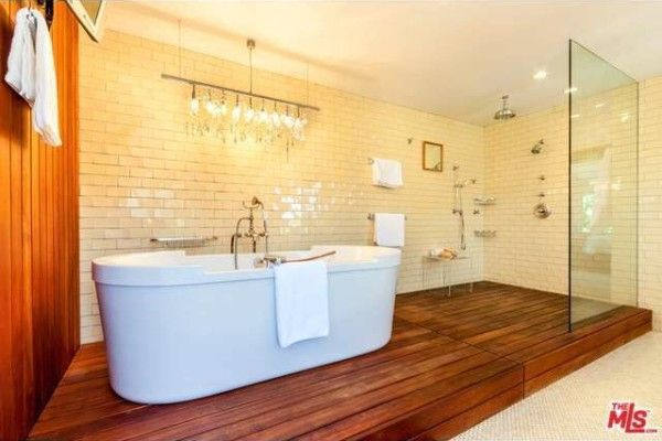 A dramatic lighting fixture hangs over the bathtub.