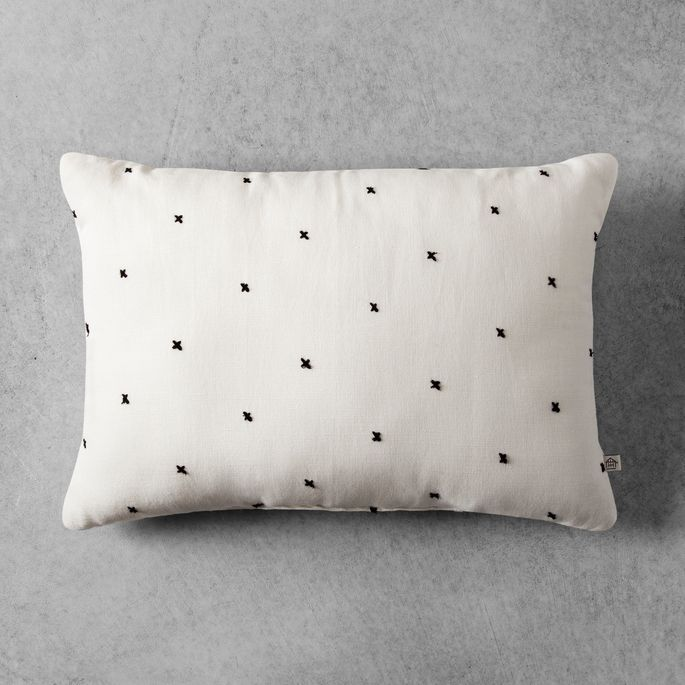 The neutral color and sweet embroidered detail make this pillow a must-buy.
