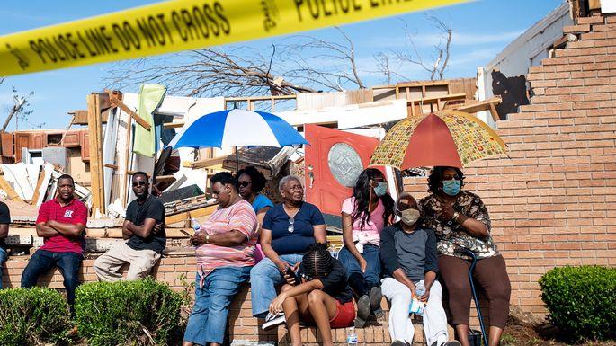 Family, friends, and neighbors sit in front of a destroyed home in Nixville, SC.