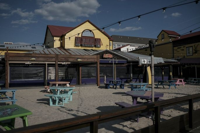 Tables are set aside in anticipation of outdoor dining at reduced capacity at an empty Fish Tales restaurant in Ocean City, Md.
