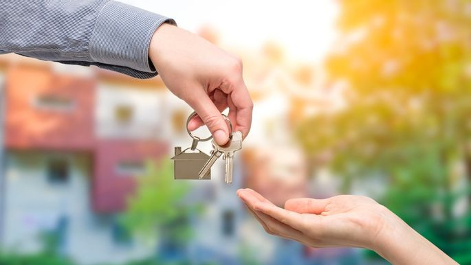 Man handing a house key to woman. Real estate concepts.