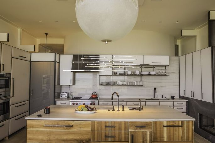 In the kitchen, cabinets are upholstered in woven vinyl and the white stone on the wall behind the stove is polished to allow a reflection of the lake.