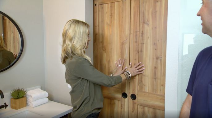 This wood door gives the bathroom an earthy feel.