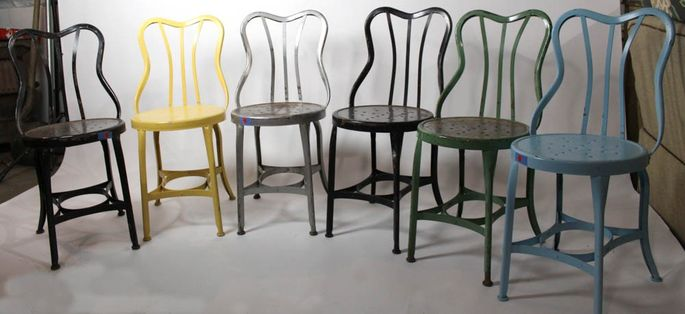 Colorfully painted metal cafe chairs on auction