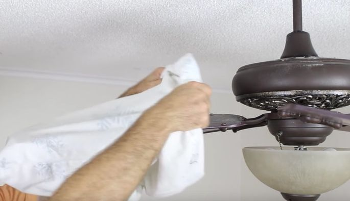 Use a pillowcase to clean a ceiling fan you can safely reach.