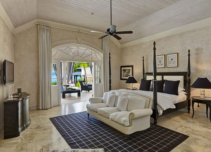 A bedroom with a high ceiling and view of the sea
