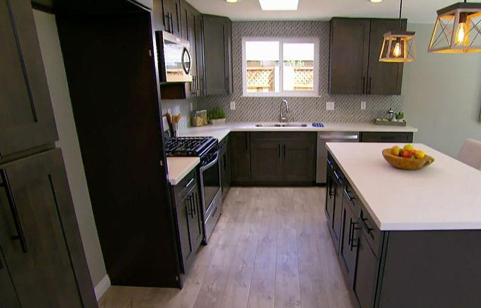 The kitchen with brown/gray cabinets and backsplash