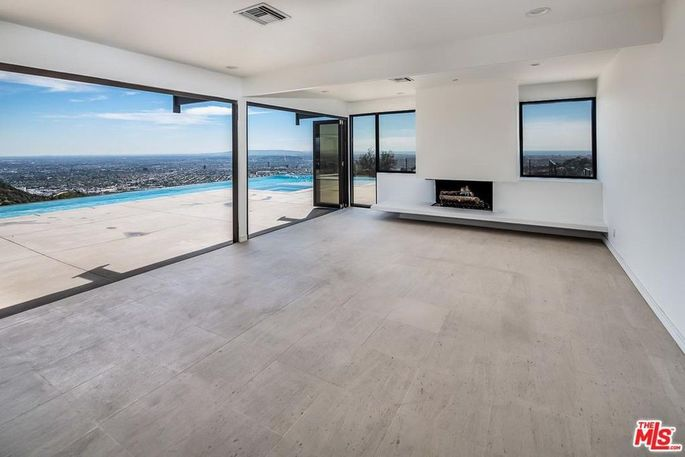 Contemporary living room opens to pool deck.