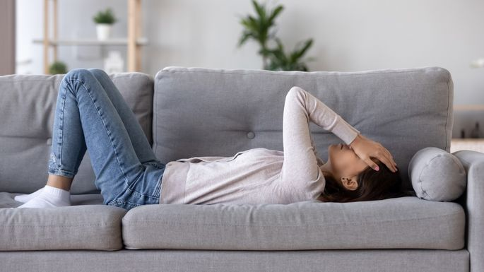 Full length young woman lying on couch suffers from heartache