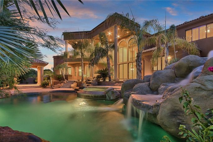 The backyard features a patio, pool, and boulder slide.